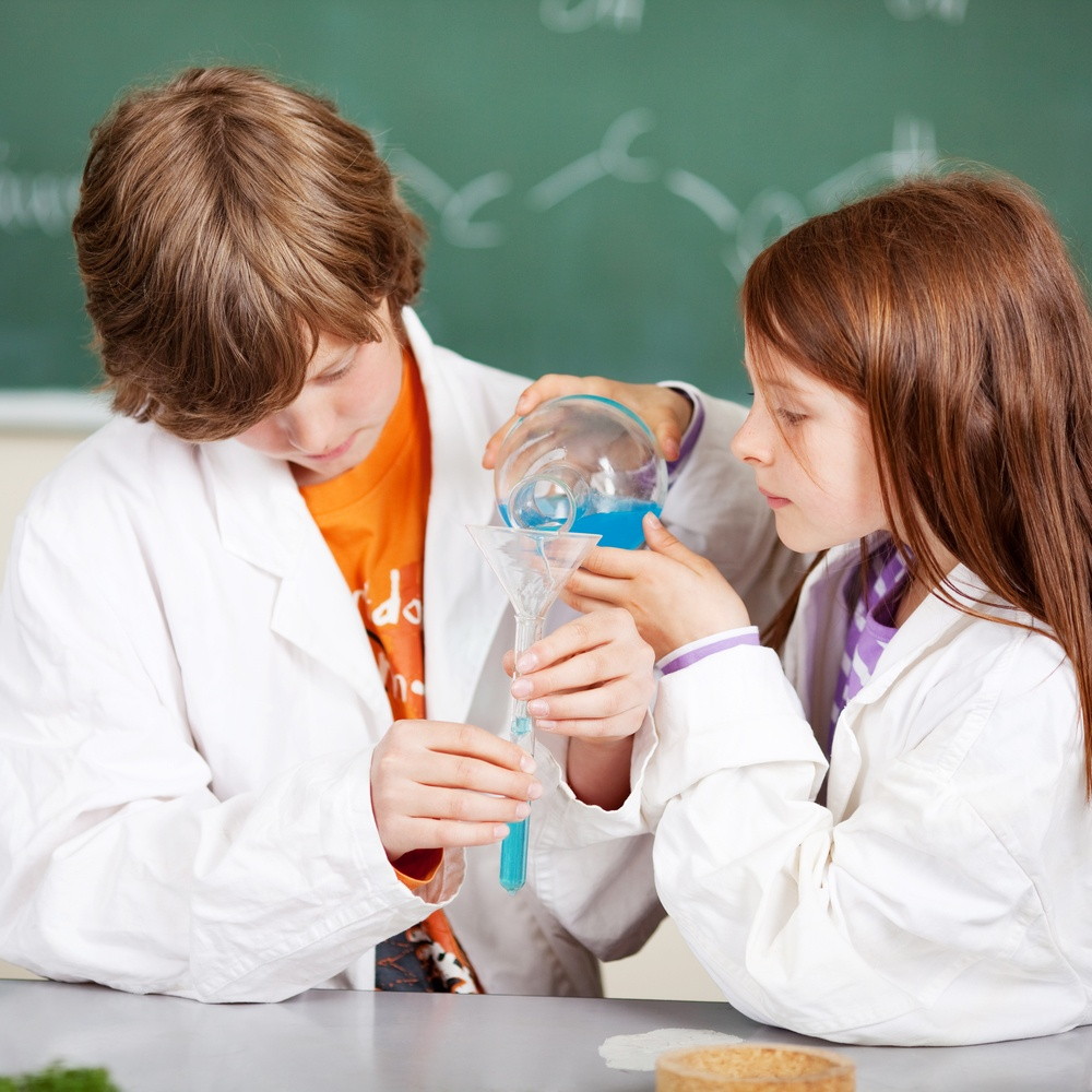 Young boy and girl in school learning chemistry working together as a team pouring liquids through a funnel into a test tube.jpeg